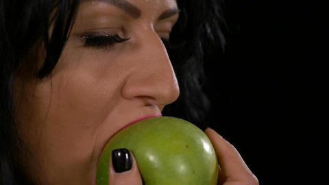 Slow motion of beautiful healthy woman biting and eating a fresh green apple Footage