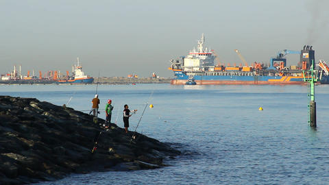Fisherman group on stony shore, large dredger vessel move on background Footage