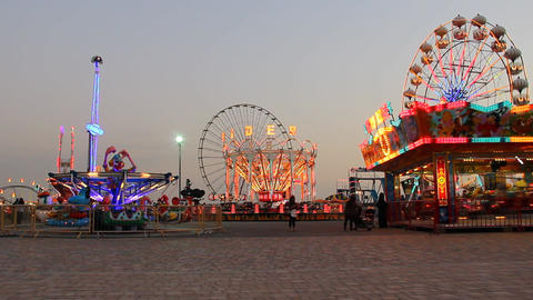 Dubai Festival City playground area, bright illuminated attractions at dusk Live Action