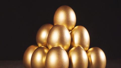 Golden eggs. Gold eggs on black background Image