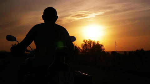 The biker turns to the right at sunset and leavest 画像