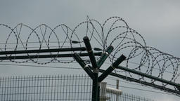 Security fence with a barbed wire with grey sky. Fence with a barbed wire Image