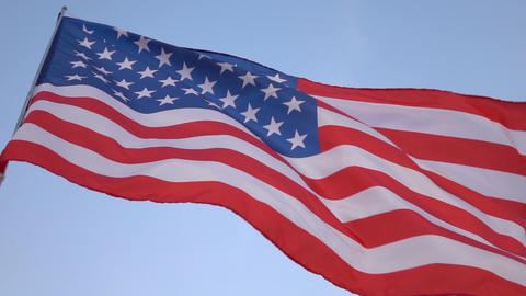 American flag in the wind on blue sky, slow motion Archivo