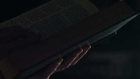 Female reading a holy bible book at night Footage