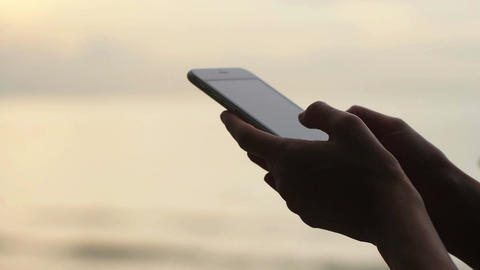 Woman typing text message near sea in the morning Footage