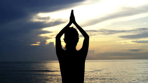 Silhouette woman practicing yoga at sea in sunrise Image