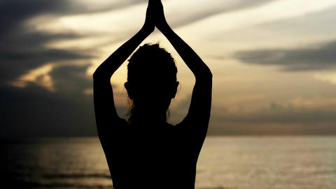 Silhouette female practicing yoga at sea in the sunrise Footage