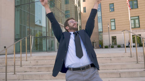 Male office worker in a suit crazy dancing and celebrating success outside his Footage