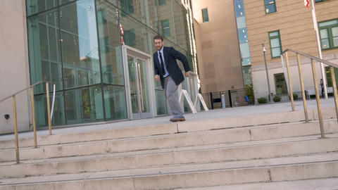 Handsome millennial businessman dancing down steps celebrating achievement and Live Action