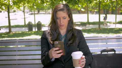 Happy attractive businesswoman sitting on park bench smiling and drinking coffee Footage