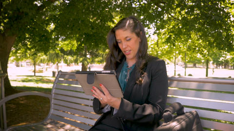 Beautiful businesswoman working on her digital tablet touchpad outside in park Footage