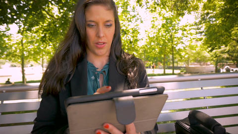 Beautiful brunette millennial businesswoman on digital touchpad tablet thinking Footage