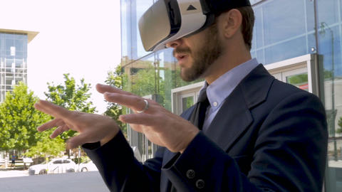 Camera circles a happy smiling handsome businessman wearing a VR headset virtual Footage