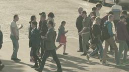 Many people cross the street on a pedestrian crossing. Slow motion Footage