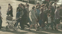 Many people cross the road on a pedestrian crossing. Slow Motion Footage