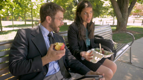 Handsome millennial man and pretty woman both in business attire eating healthy Footage