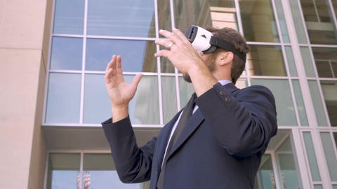 Attractive corporate millennial 30s businessman with VR headset experiencing Footage