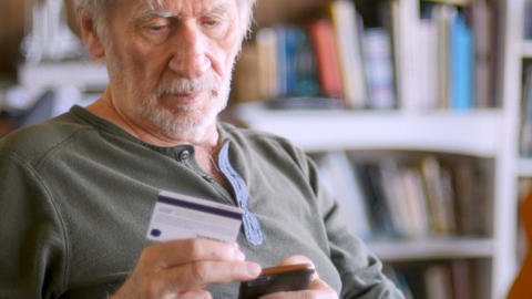 Attractive elderly 60s or 70s man entering credit card numbers into his smart Footage
