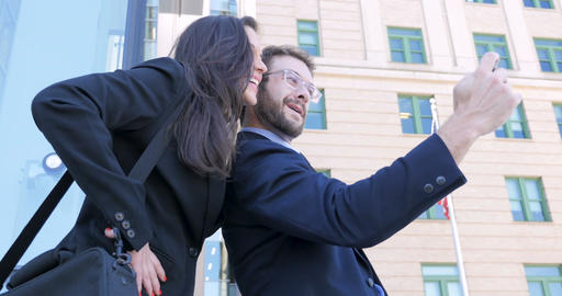 Two young 30s coworkers take a selfie outside skyscrapers with an American flag Footage