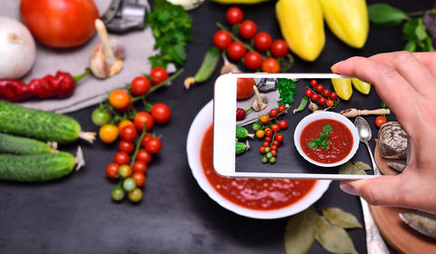 Female hand with smartphone in hand photographs soup gazpacho Photo