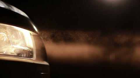 Bright car headlights in clouds of dust at night Filmmaterial