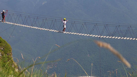 Tourists are walking along a suspension bridge over an abyss Filmmaterial