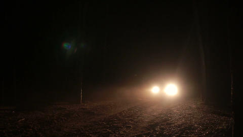 Headlights of car approaching on a dark road Footage