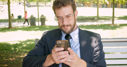 Portrait of successful businessman texting and reading mobile phone sitting on Footage