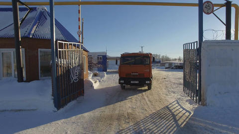 Camera Moves up from Red Kamaz Lorry Driving Through Gate Footage