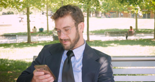 Happy smiling handsome business man with beard and eyeglasses reading emails or Footage