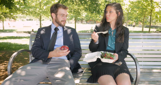 Two attractive young millennial business office executives sitting in a park Footage