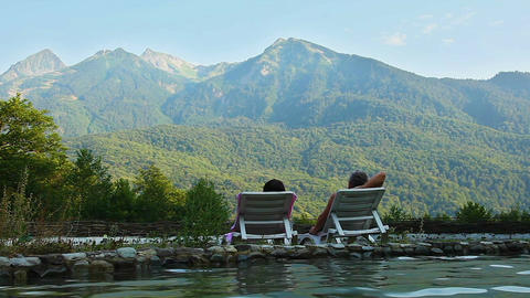 Сouple relaxes lying by the lake in the background of the mountains Image