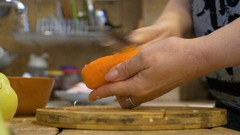 Closeup of middle aged woman peeling a carrot at home in kitchen using tradition Footage