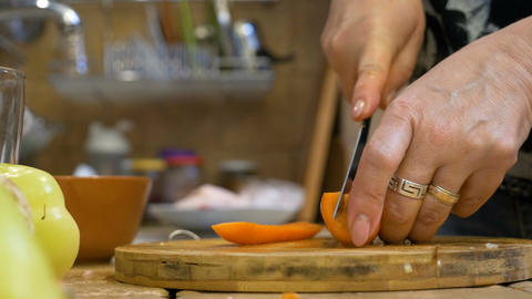 Adult woman wife in kitchen cutting fresh carrot preparing a vegetable dish Live Action