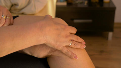 Closeup of mature married woman carefully massaging her rheumatic knee at home i Footage
