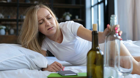 Boozy young woman waking up in bed after party Footage