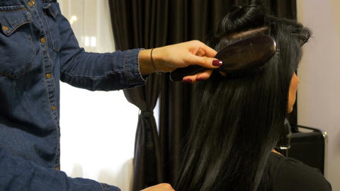 Hairdresser brushing the hair of a woman sitting in front of her at beauty salon Footage