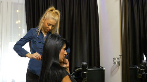 Business woman talking at the mobile phone while getting a hairdo at beauty Footage