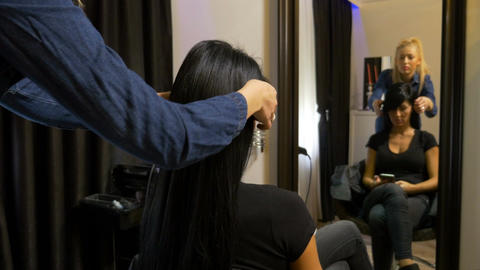 Hairdresser getting beautiful woman prepped for event Footage