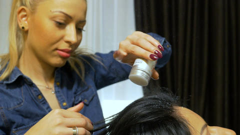 Hairstylist applying styling powder on client hair at beauty salon after Footage