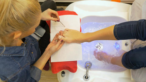 Woman getting her pedicure done by a specialist at beauty salon Footage