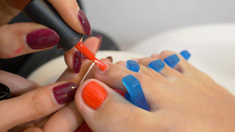 Close up with nail art technician applying red nail polish on toe nails of Footage