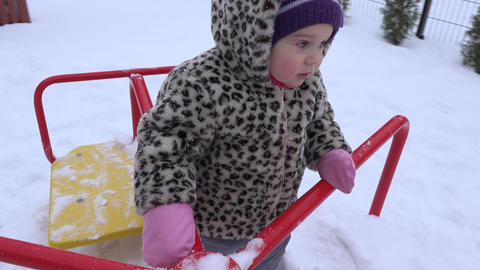 little baby girl swing in playground at snowy winter time. 4K Footage