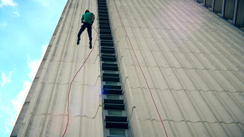 Fearless man descend down with cord on skyscraper wall. Blue cloudy sky Footage