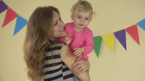 attractive mother is holding cute happy, laughing baby girl in arms and dancing Footage