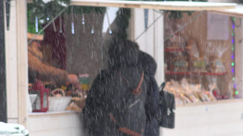 People buy souvenirs food and drinks in christmas town fair kiosk. Snow falling Footage