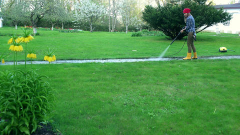 Gardener woman washing footpath with high pressure water jet Footage