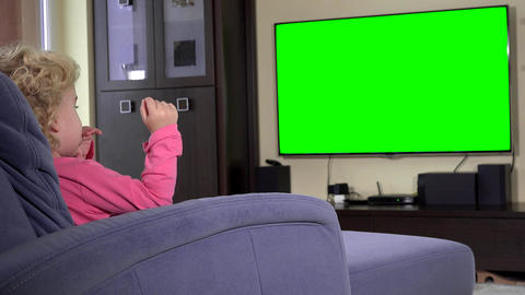 child sit in front of a tv and watch a children show on. Green chroma key screen Footage
