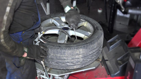 dirty worker hands inflate tire air wit compressor on mounting machine Footage
