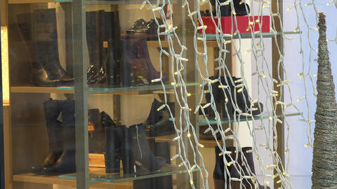 Closeup of shoes shop glass case with white string lights. Christmas sale out Footage